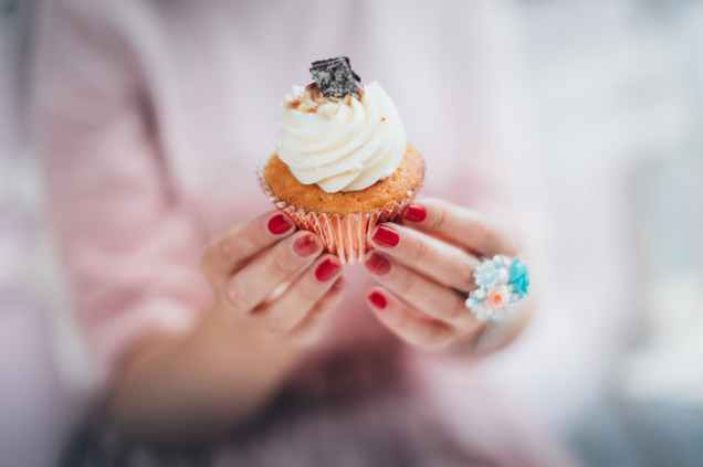 woman holding cupcake with cream
